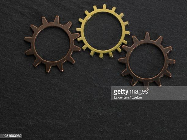 close-up of gears on black table - three objects stock pictures, royalty-free photos & images
