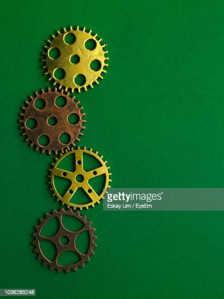 Close-Up Of Gears On Green Table