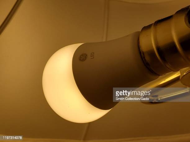 Closeup of General Electric brand energy efficient LED lightbulb installed in tabletop lamp San Ramon California January 2 2020