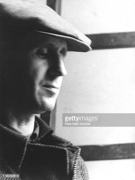 Closeup of German playwright and poet Bertolt Brecht in front of a window with cap on his head Paris France 1937