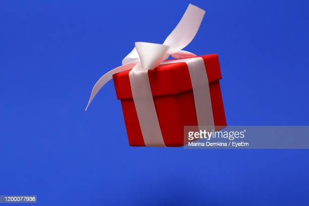 close-up of gift box against blue background - marina weisband stock-fotos und bilder