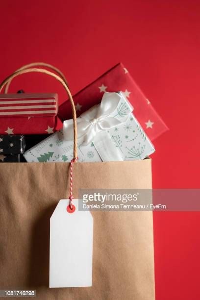 close-up of gift boxes in paper bag against red background - christmas still life stock pictures, royalty-free photos & images