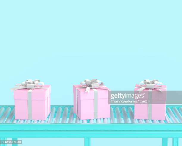 close-up of gift boxes on conveyor belt against blue background - automated stock pictures, royalty-free photos & images