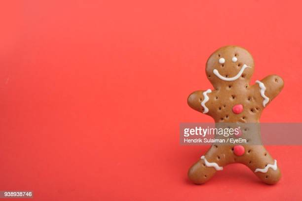 close-up of gingerbread cookie over coral background - gingerbread man stock photos and pictures