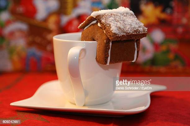 Close-Up Of Gingerbread House On White Coffee Cup