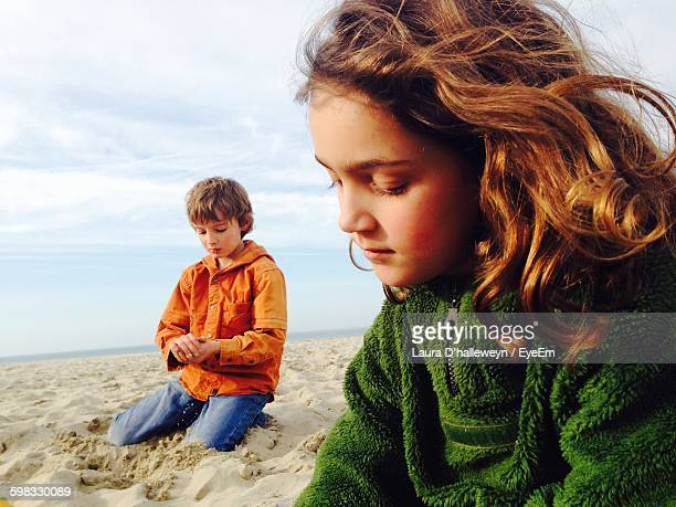 Close-Up Of Girl And Boy Sitting On Beach Against Sky