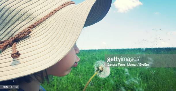 Close-Up Of Girl Blowing Dandelion