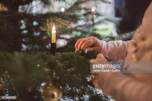Close-Up Of Girl Decorating Christmas Tree