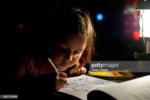 close-up of girl drawing on book in darkroom at home - art and craft stock pictures, royalty-free photos & images
