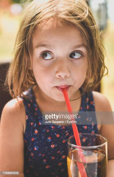 Close-Up Of Girl Drinking Apple Juice While Looking Away At Outdoor Restaurant