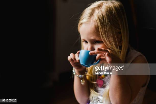 Close-up of girl drinking tea while playing at home