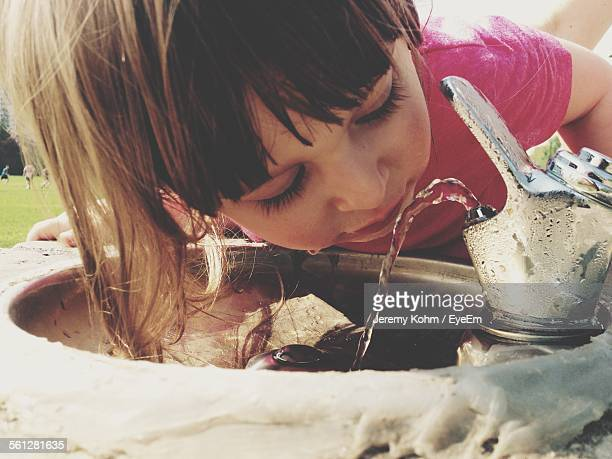 Close-Up Of Girl Drinking Water From Faucet Outdoors