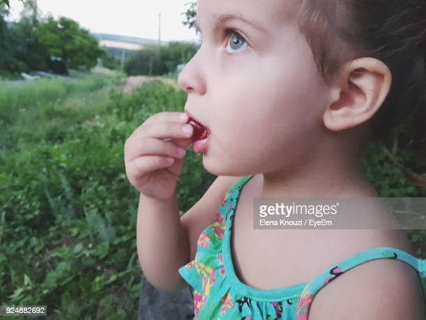 close-up of girl eating cherry while standing by plants - elena knouzi stock pictures, royalty-free photos & images