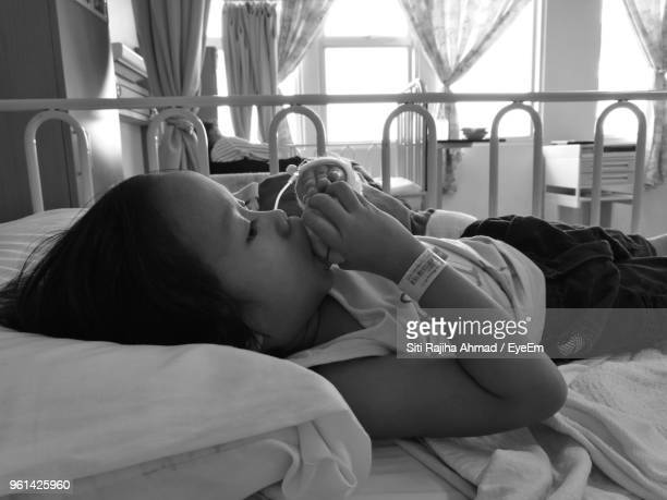 Close-Up Of Girl Eating Fruit While Lying On Bed In Hospital