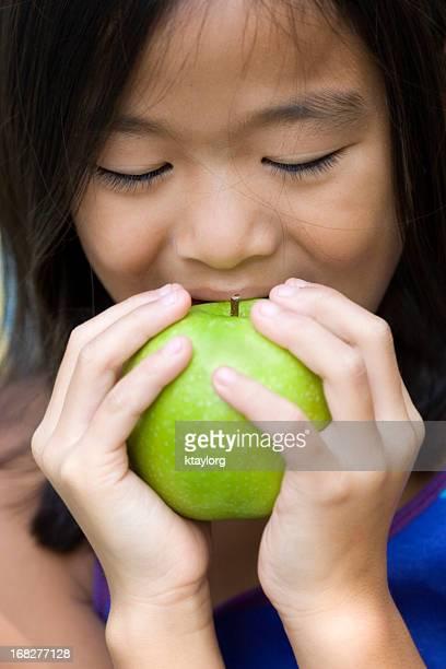 Closeup of girl eating green apple