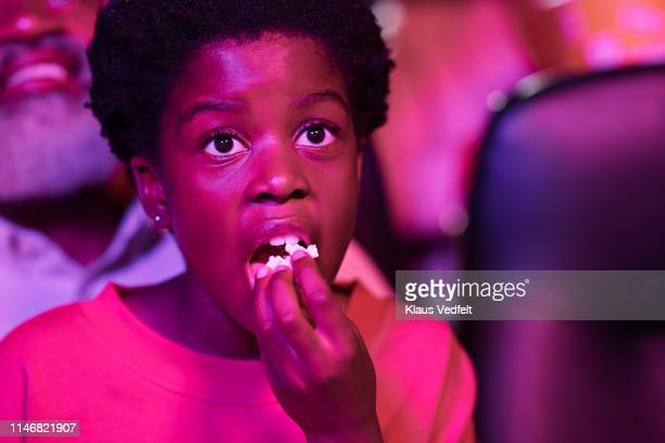 close-up of girl eating popcorn while watching movie in cinema hall - hot pink stock pictures, royalty-free photos & images