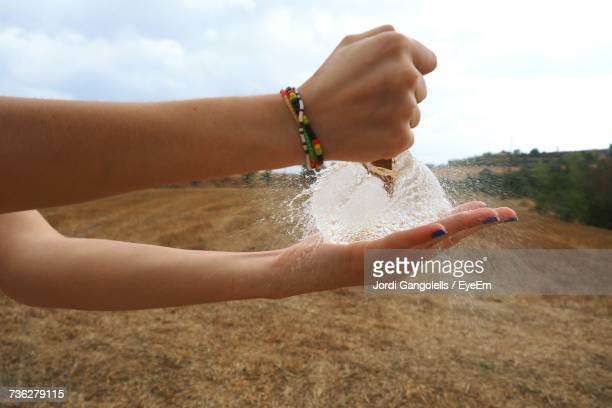 Close-Up Of Girl Hand On Sand Against Sky