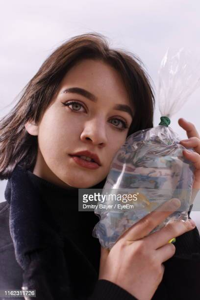 Close-Up Of Girl Holding Fish In Plastic Bag While Looking Away Against Sky