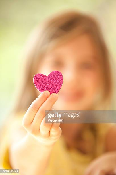 Close-up of girl holding glittering heart