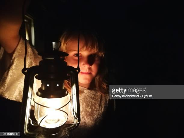 close-up of girl holding illuminated oil lamp in darkroom - oil lamp stock pictures, royalty-free photos & images