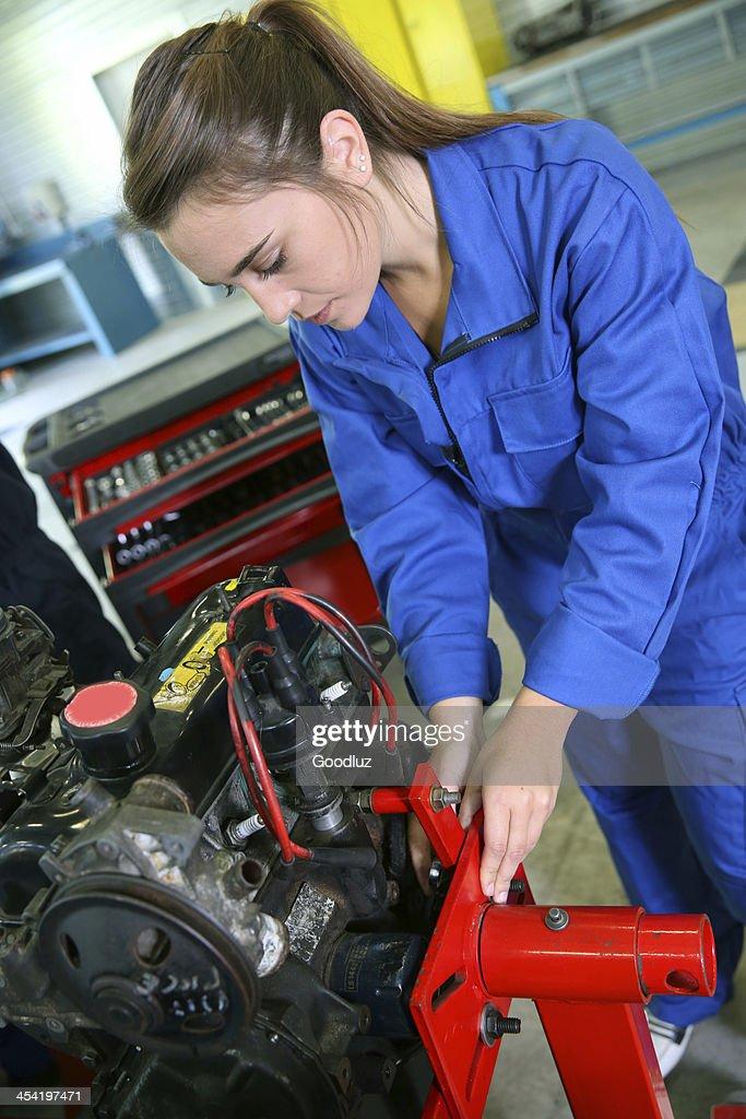 Plano aproximado de menina em azul dungarees trabalhar na garagem : Foto de stock