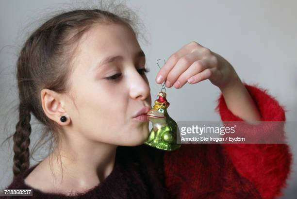 Close-Up Of Girl Kissing Frog Ornament