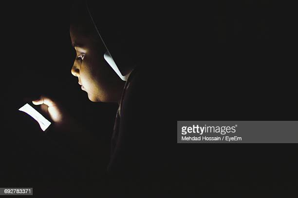 Close-Up Of Girl Listening To Music While Using Phone In Darkroom