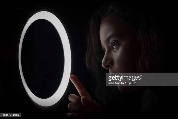 close-up of girl looking at illuminated circle against black background - angel halo stock pictures, royalty-free photos & images