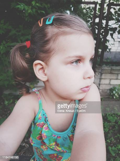 close-up of girl looking away outdoors - elena knouzi stock pictures, royalty-free photos & images