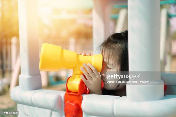 Close-Up Of Girl Looking Through Toy Telescope While Playing At Playground