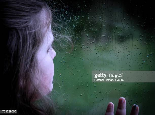 close-up of girl looking through wet window during rainy season - heather storm stock photos and pictures