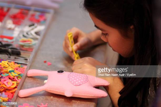Close-Up Of Girl Making Toy At Table