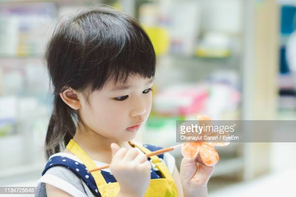 close-up of girl painting flower - chanayut stock photos and pictures