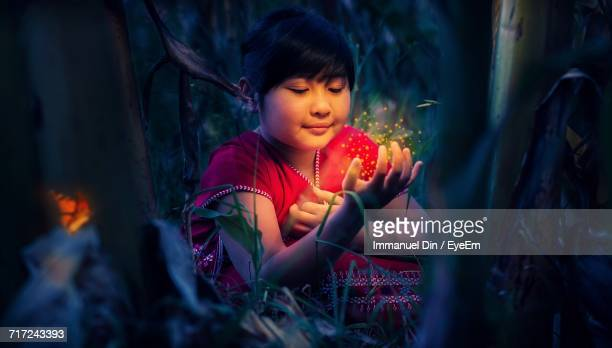Close-Up Of Girl Playing With Fireflies On Grassy Field At Night