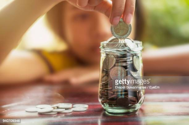 close-up of girl putting coins in full jar at table - jar stock pictures, royalty-free photos & images