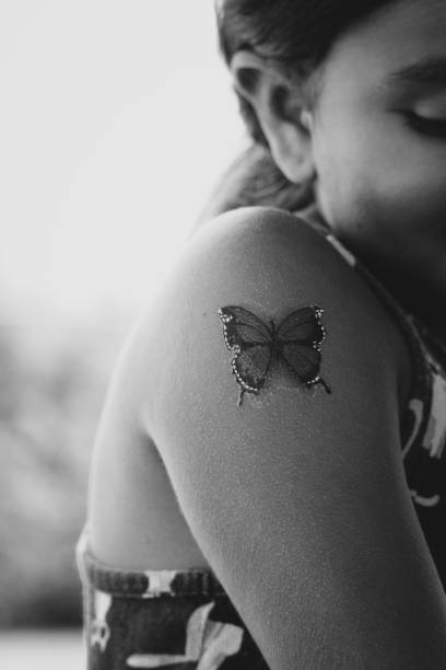 Close-Up Of Girl Shoulder With Butterfly Tattoo