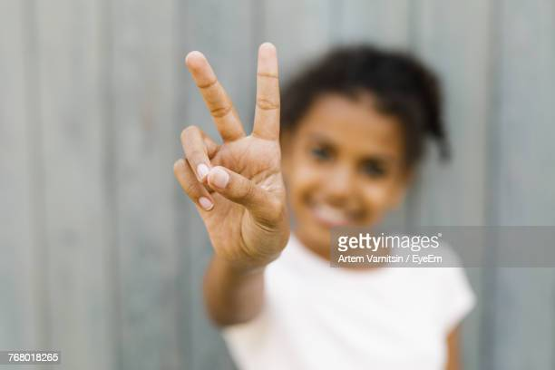 Close-Up Of Girl Showing Peace Sign