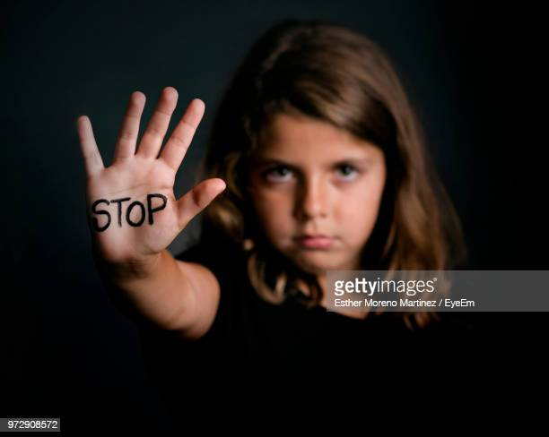 close-up of girl showing stop text on palm against black background - anti bullying symbols stock pictures, royalty-free photos & images