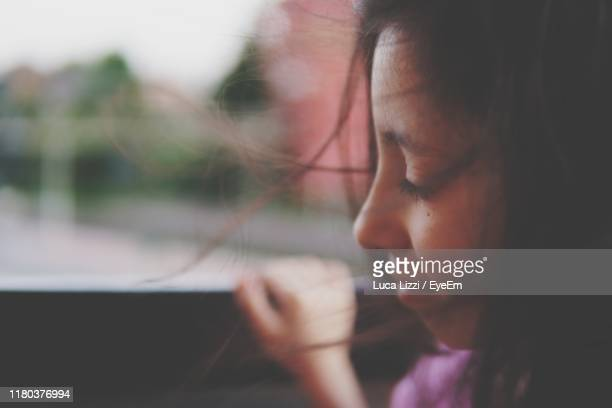 close-up of girl sitting in car - innocence stock pictures, royalty-free photos & images
