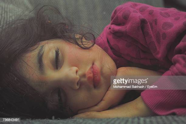 Close-Up Of Girl Sleeping On Sofa