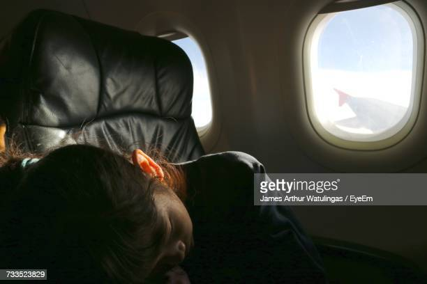 Close-Up Of Girl Sleeping While Traveling In Airplane