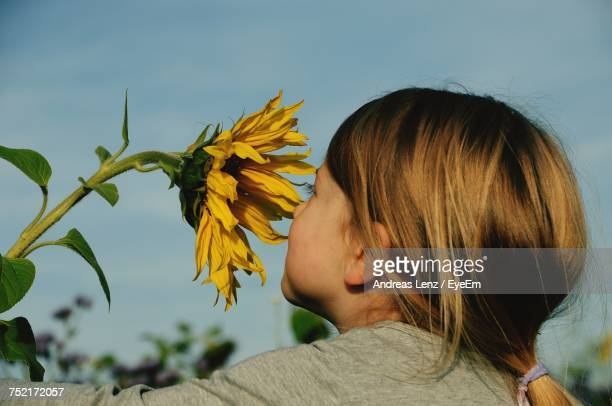 Close-Up Of Girl Smelling Sunflower Against Sky At Park