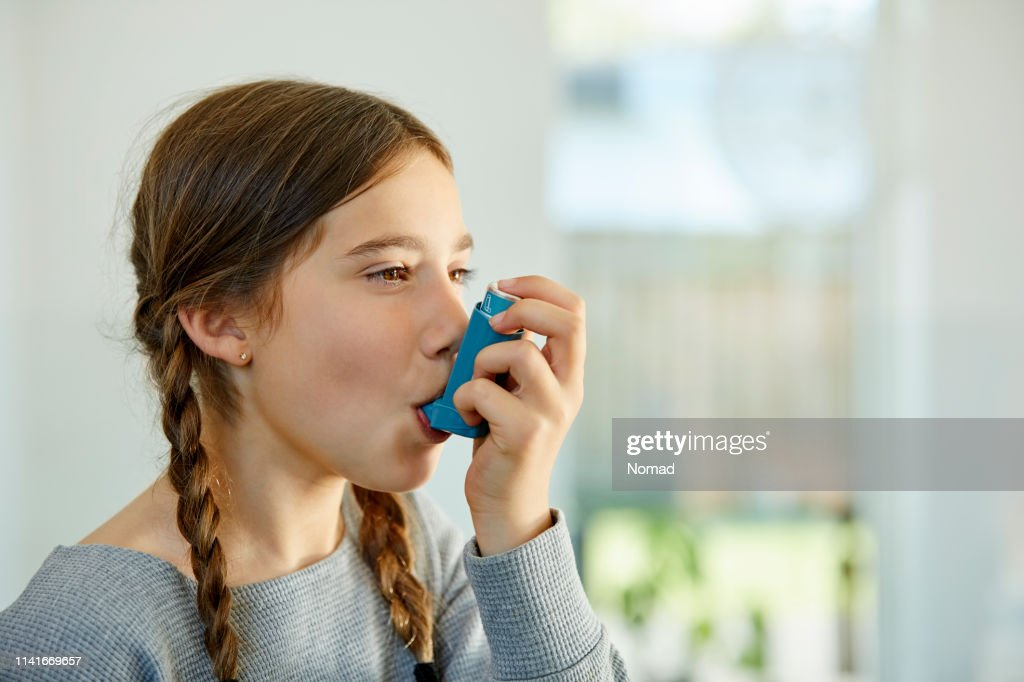 Close-up of girl using asthma inhaler at home : Stock Photo