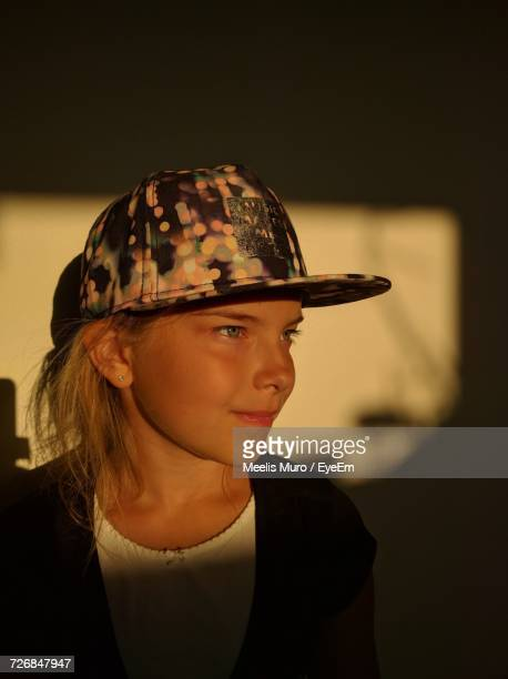 close-up of girl wearing cap standing against wall - muro stock photos and pictures