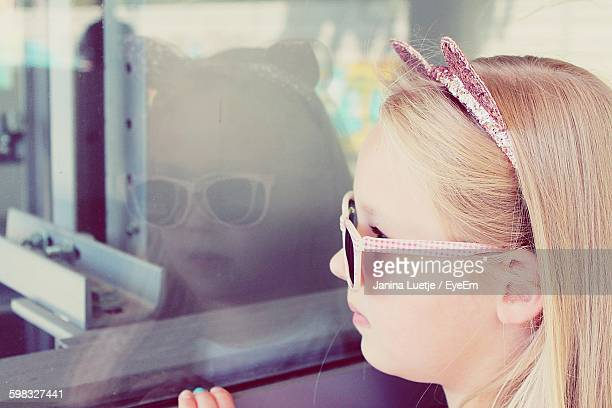close-up of girl wearing cat ears looking through window - cat costume stock photos and pictures
