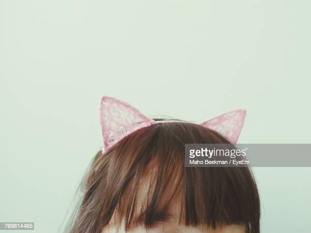 Close-Up Of Girl Wearing Headband Against White Background