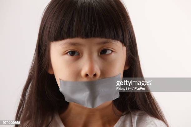 close-up of girl with adhesive tape on mouth against white background - innocence stock-fotos und bilder