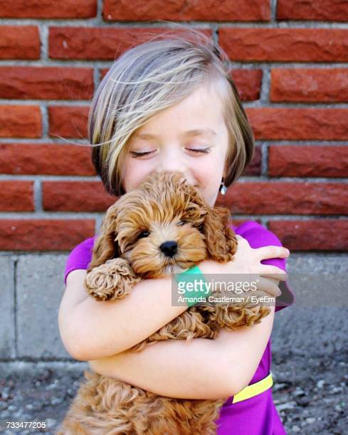 Close-Up Of Girl With Dog Standing Against Brick Wall