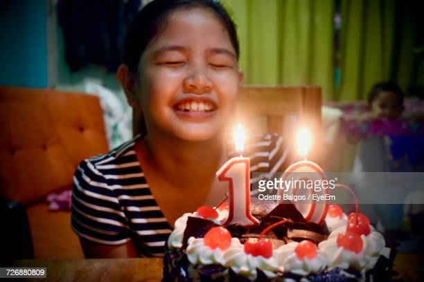 Close-Up Of Girl With Eyes Closed By Birthday Cake