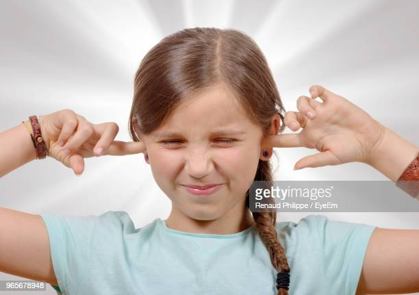 close-up of girl with fingers in ears against wall - fingers in ears stock pictures, royalty-free photos & images